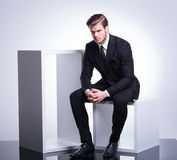 Business man sitting on a cube holding his hand together, Royalty Free Stock Images