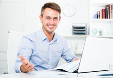 Business man sitting with document in office Stock Images