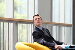 Business man sitting with documents folder open looks up the window Royalty Free Stock Photography