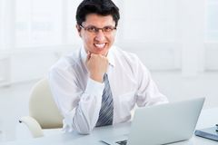 Business man sitting in front of laptop. Happy business man sitting in front of laptop Royalty Free Stock Photos
