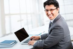 Business man sitting in front of laptop. Happy business man sitting in front of laptop Stock Photography