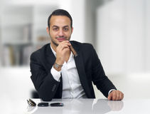 Business man sitting in his office and smoking cigar Stock Photography