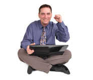 Business Man Sitting with Laptop. A handsome business man is sitting on the floor and holding a laptop internet computer. His hand is in the air and he is Stock Images