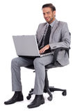 Business man sitting with laptop and smiling Stock Photos