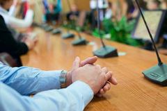 Business man sitting at a meeting with her hands folded Stock Image