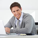 Business man sitting in office. Smiling business man sitting in office with his laptop Stock Photography