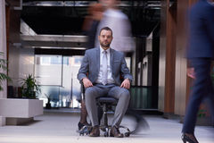 Business man sitting in office chair, people group  passing by Stock Photos