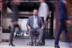 Business man sitting in office chair, people group  passing by Stock Image