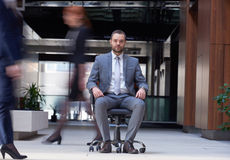 Business man sitting in office chair, people group  passing by Royalty Free Stock Photography