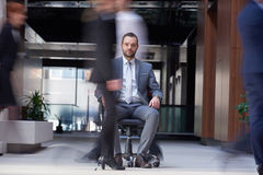 Business man sitting in office chair, people group  passing by Stock Photo