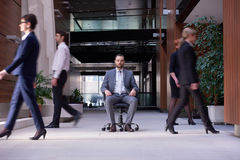 Business man sitting in office chair, people group  passing by Royalty Free Stock Photo