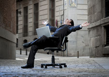 Business Man sitting on Office Chair on Street with Computer Stock Image