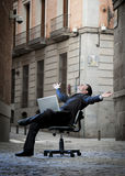 Business Man sitting on Office Chair on Street with Computer Stock Photos