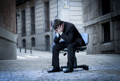 Business Man sitting on Office Chair on Street in stress Royalty Free Stock Images