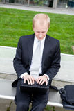 Business man sitting outdoor working with notebook Stock Images