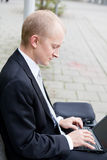 Business man sitting outdoor working with notebook Royalty Free Stock Photo