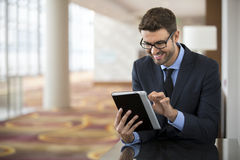Business man sitting reading a tablet device Stock Photo