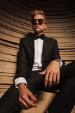 Business man sitting while relaxing his hands on his legs. Royalty Free Stock Photography