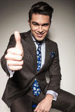 Business man sitting while showing the thumbs up gesture Stock Photography