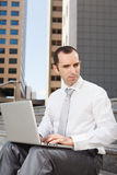 Business man sitting on steps using laptop. Low angle view Stock Images
