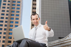 Business man sitting on steps using laptop thumb up. Business man sitting on steps using laptop, low angle view Stock Photography