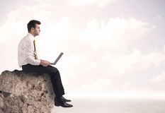 Business man sitting on stone edge Stock Photo