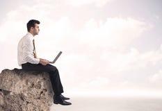 Business man sitting on stone edge Stock Photo