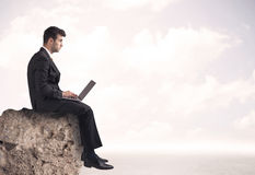 Business man sitting on stone edge Stock Image