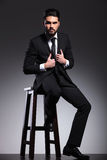 Business man sitting on a stool arranging his jacket Stock Images