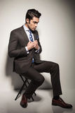 Business man sitting on a stool while fixing his jacket Royalty Free Stock Photos
