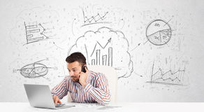 Business man sitting at table with hand drawn graph charts Royalty Free Stock Images
