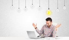 Business man sitting at table with idea light bulbs Stock Photos