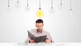 Business man sitting at table with idea light bulbs Stock Image