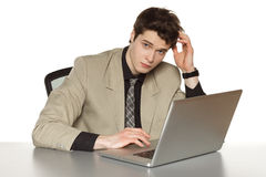 Business man sitting at the table with laptop. Young business man sitting at the table with laptop, scratching his head, over white background Royalty Free Stock Images