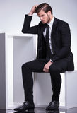 Business man sitting on a table while scratching his head Royalty Free Stock Image