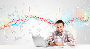 Business man sitting at table with stock market graph Royalty Free Stock Photography