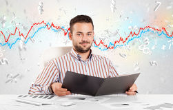 Business man sitting at table with stock market graph Stock Images