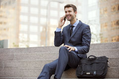 Business man sitting talking on cell phone Royalty Free Stock Photo