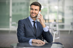 Business man sitting talking on cell phone. A successful business man in a suit is sitting and smiling while talking on a cell phone outdoors downtown Stock Photo