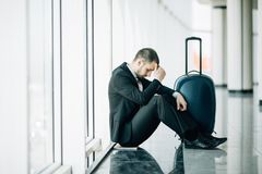 Business man sitting at the terminal airport on the floor with suitcase flight delay, two hands touch at head, headache, waiting t. Raveling stock photography