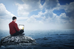 Business man sitting on the top of the rock. In the middle of the sea Stock Images