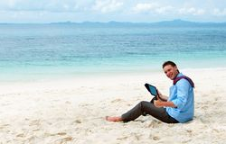 Business man sitting and working on the beach Stock Photo