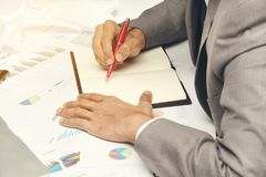 Business man sitting writing text note and use red pen on work t. Business man sitting writing text note black cover on graph diagram paper, he wear gray suit Stock Photo