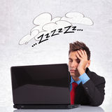 Business man sleeping on his office desk. Young business man sleeping on his office desk with laptop Stock Images