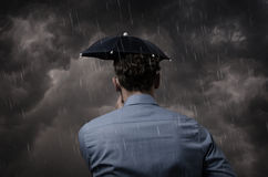 Business man with small umbrella Stock Images