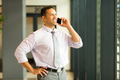 Business man on smart phone. Cheerful business man talking on smart phone in office Stock Photography