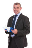 Business man smiles while holding his clipboard Royalty Free Stock Photos