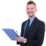 Business man smiles with pen and clipboard Stock Photography