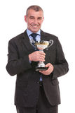 Business man smiles with trophy in hands Stock Photography