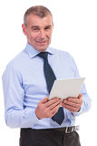 Business man smiles at you with tablet in hand Royalty Free Stock Photos
